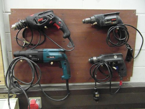 Different handheld electric drills on the wall.